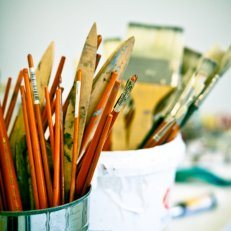 Artist supplies, including brushes and pencils, upright in cups.