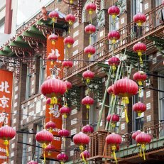 Red paper lanterns strung along the side of a building