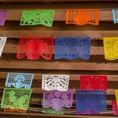 Colorful cutouts, papel picado, strung across a ceiling