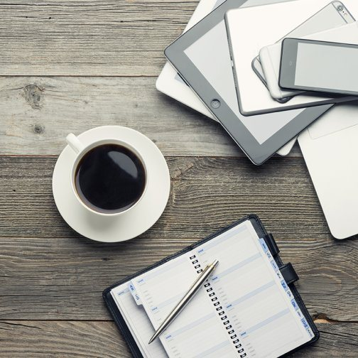 A cup of coffee, notebook and mobile devices sitting on a table.