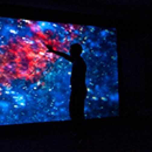 Silhouette of a person standing in front of a lit image of outer space.
